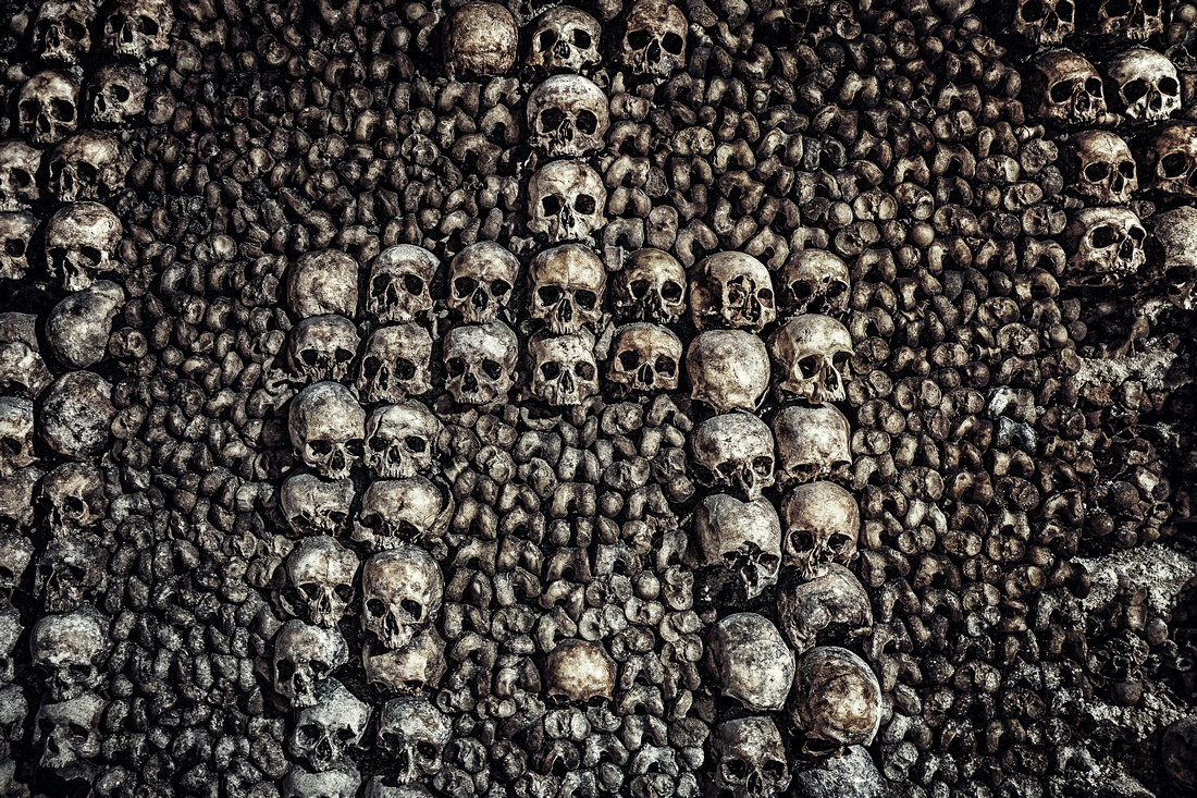 The bones and skulls of human remains stacked to form a wall and macabre art.